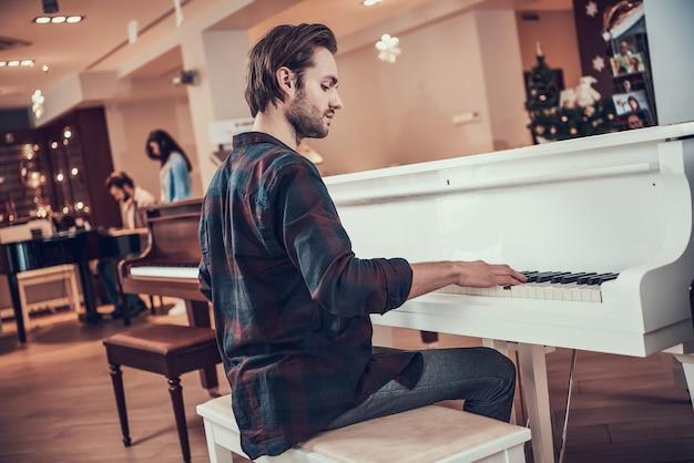 Jovem bonito toca piano na loja de instrumentos musicais