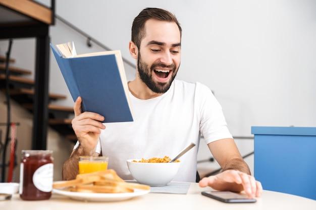 Jovem bonito tomando café da manhã enquanto está sentado na cozinha, lendo um livro