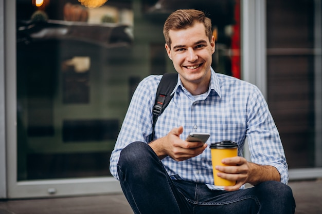 Jovem bonito tomando café lá fora