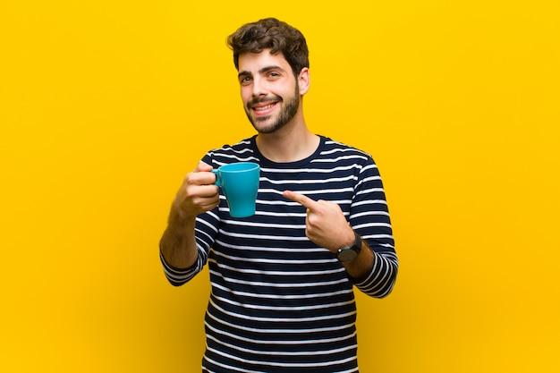 Jovem bonito tomando um café contra laranja