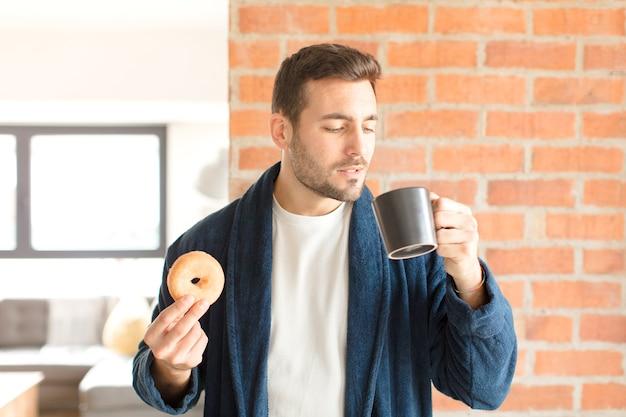 Jovem bonito tomando um café em casa