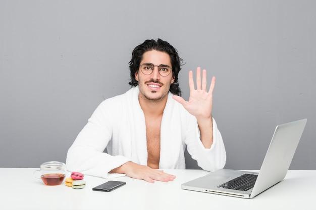 Jovem bonito, trabalhando após um banho, sorrindo alegre mostrando o número cinco com os dedos.