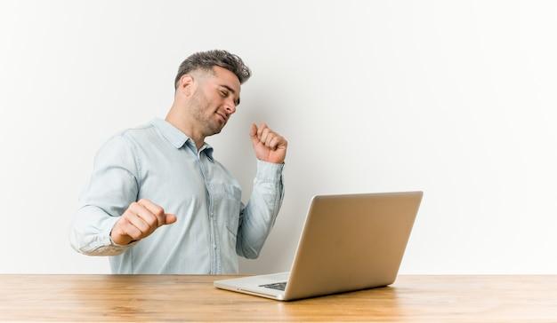 Jovem bonito, trabalhando com seu laptop, dançando e se divertindo