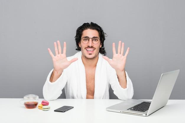 Jovem bonito trabalhando depois de um banho, mostrando o número dez com as mãos.