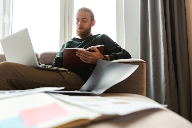 Jovem bonito trabalhando em casa, sentado em um sofá usando um laptop