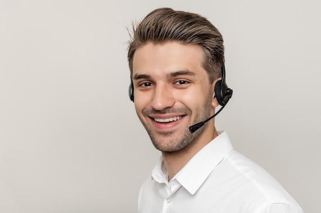 Jovem bonito trabalhando em um call center com fones de ouvido e sorrindo