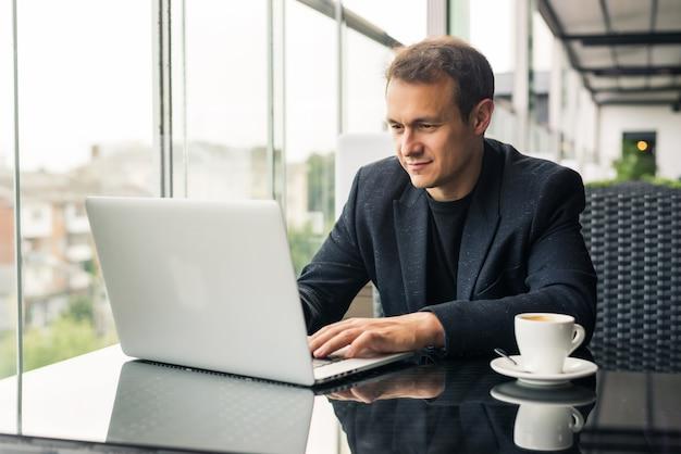 Jovem bonito trabalhando em um laptop e sorrindo enquanto está sentado em um café na calçada