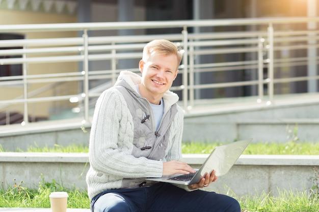 Jovem bonito trabalhando em um laptop e sorrindo na rua da cidade