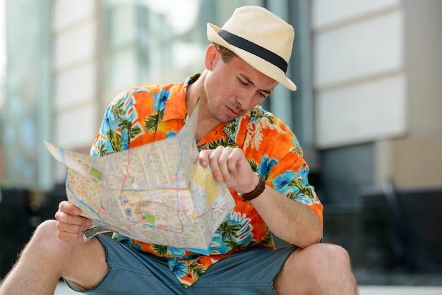 Jovem bonito turista com mapa, verificando a hora ao ar livre na cidade