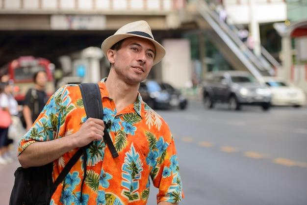 Jovem bonito turista com mochila pensando nas ruas da cidade