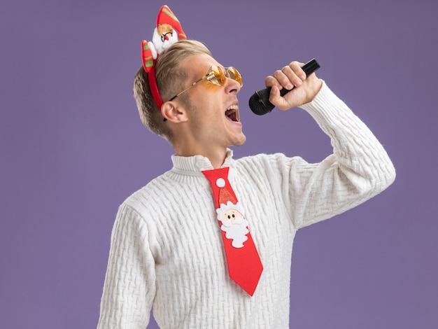 Jovem bonito usando bandana de papai noel e gravata com óculos segurando o microfone cantando com os olhos fechados, isolado em um fundo roxo com espaço de cópia