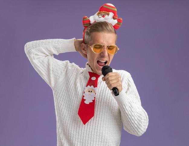 Jovem bonito usando bandana de papai noel e gravata com óculos segurando um microfone, mantendo a mão atrás da cabeça cantando com os olhos fechados, isolado no fundo roxo