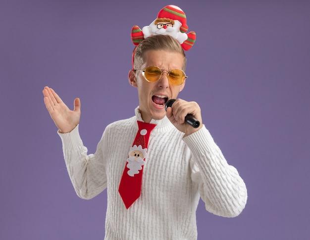 Jovem bonito usando bandana de papai noel e gravata com óculos segurando um microfone, mostrando a mão vazia cantando com os olhos fechados, isolado no fundo roxo