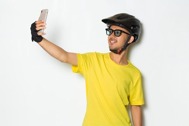 Jovem bonito usando capacete de ciclista, usando telefone celular isolado no fundo branco Foto Premium