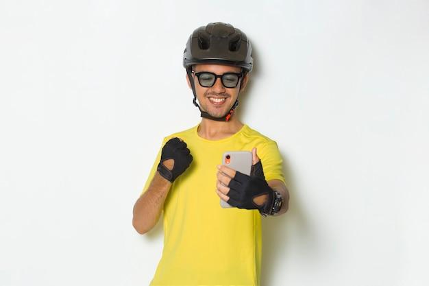 Jovem bonito usando capacete de ciclista, usando telefone celular isolado no fundo branco