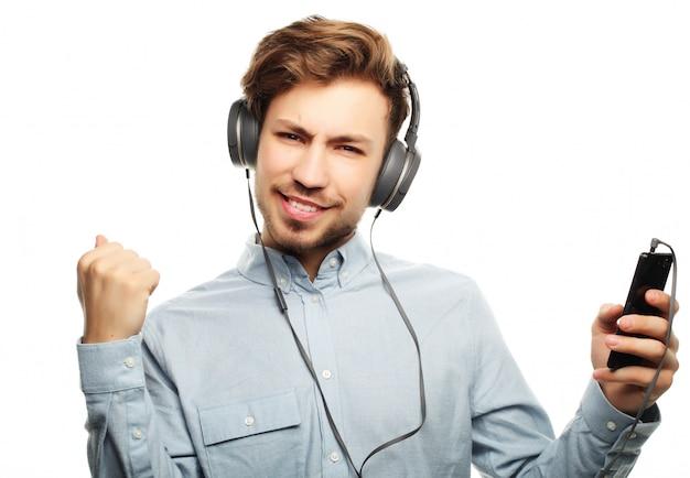 Jovem bonito usando fones de ouvido e ouvir música.