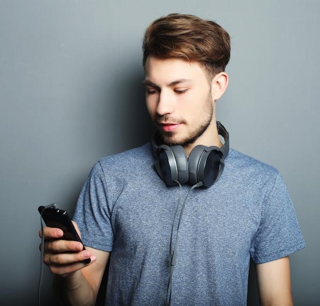 Jovem bonito usando fones de ouvido no pescoço e sorrindo