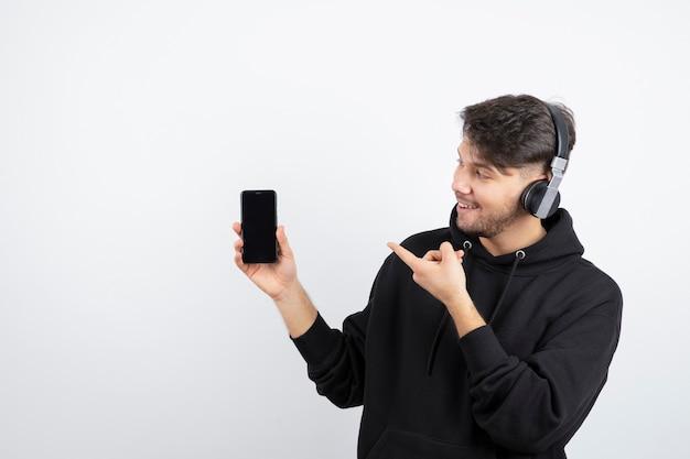 Jovem bonito usando fones de ouvido sem fio apontando para o celular