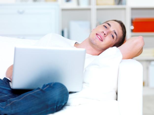 Jovem bonito usando laptop e deitado no sofá