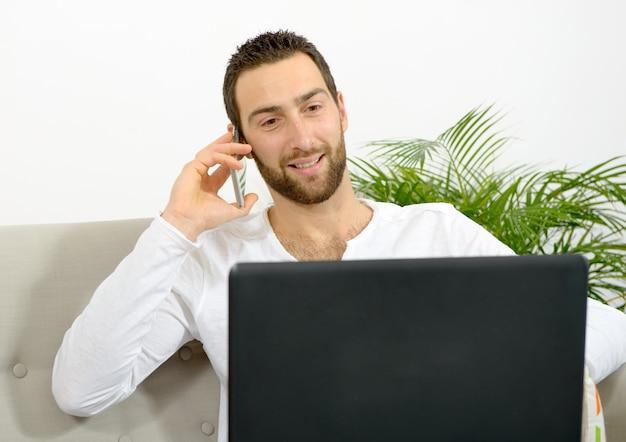 Jovem bonito usando laptop e telefone