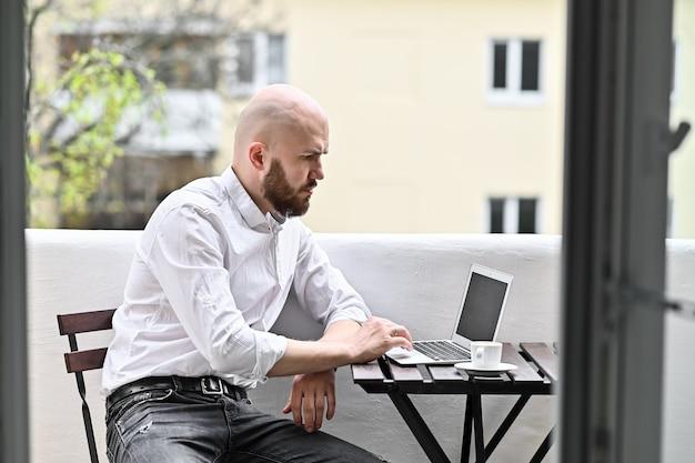 Jovem bonito usando laptop em casa, empresário ou estudante, trabalhando no conceito de educação e tecnologia de marketing online freelance online de computador