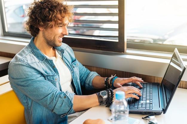Jovem bonito usando laptop enquanto almoça no bar do restaurante.
