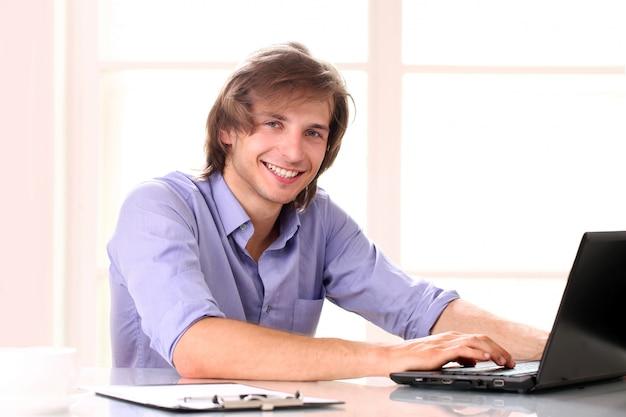 Jovem bonito usando laptop