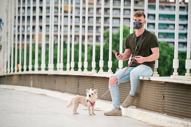 Jovem bonito usando máscara facial durante o surto de coronavírus e seu cão