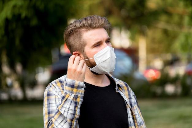 Jovem bonito usando máscara facial