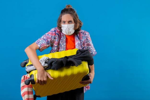 Jovem bonito usando máscara protetora facial segurando uma mala de viagem cheia de roupas, parecendo confuso, sem saber o que fazer em pé sobre um fundo azul