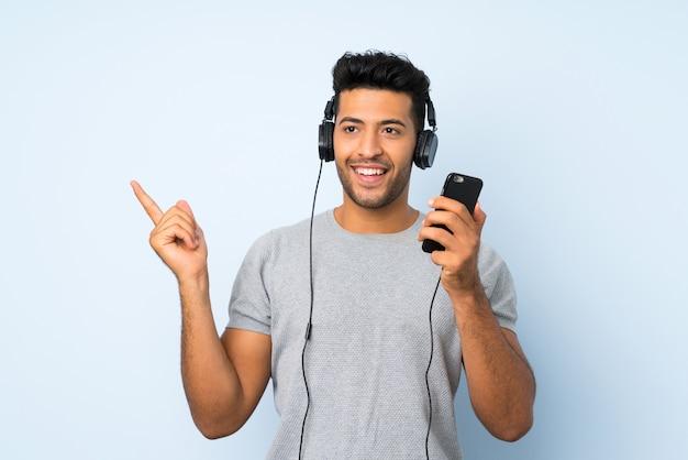 Jovem bonito usando o celular com fones de ouvido e cantando
