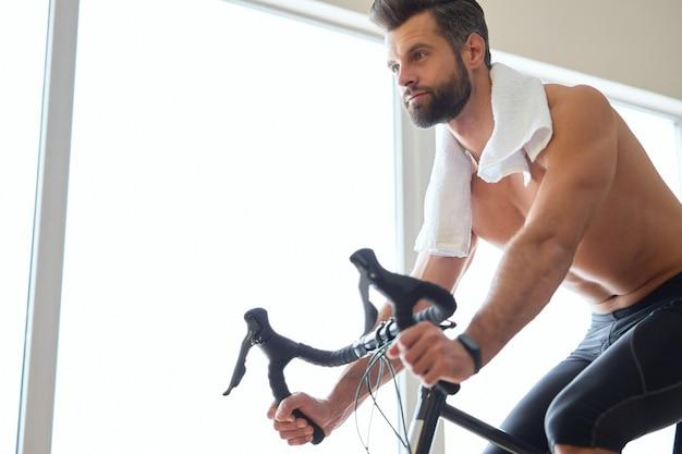 Jovem bonito usando o treinador de bicicletas em casa