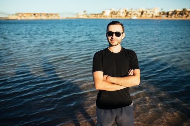 Jovem bonito usando óculos e se divertindo na praia do mar
