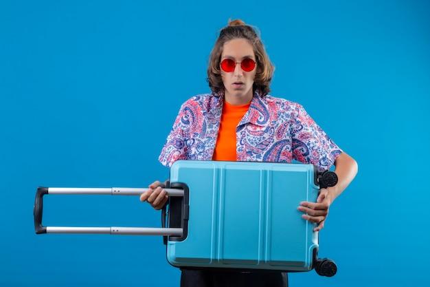 Jovem bonito usando óculos escuros vermelhos segurando uma mala de viagem, parecendo confuso em pé sobre um fundo azul