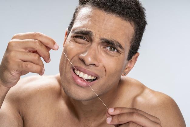 Jovem bonito usando seu fio dental e carrancudo