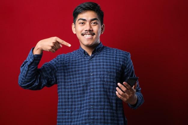 Jovem bonito usando smartphone vestindo camisa casual isolado fundo vermelho muito feliz apontando com a mão e o dedo