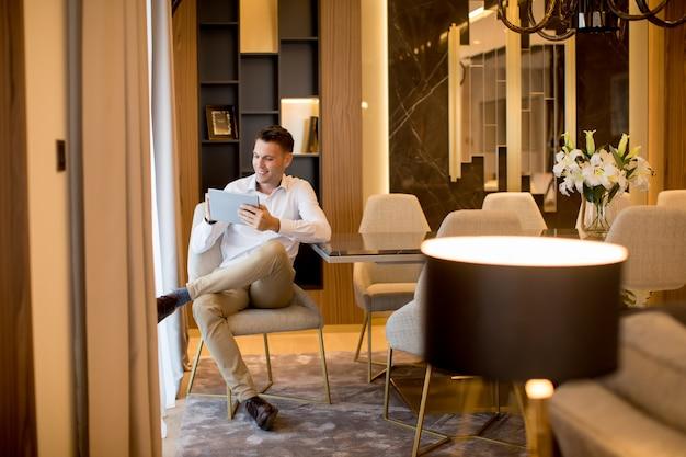 Jovem bonito usando tablet digital em apartamento de luxo