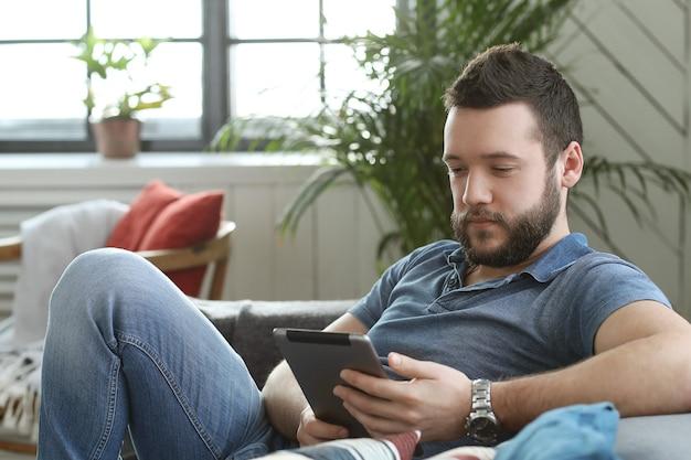 Jovem bonito usando tablet digital ou e-book