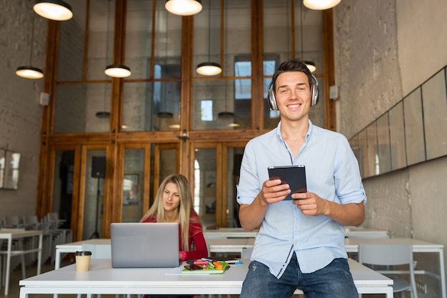 Jovem bonito usando tablet e ouvindo música em fones de ouvido sem fio,