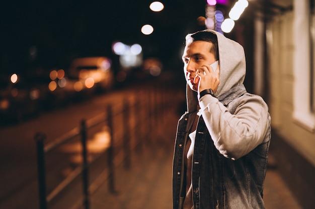 Jovem bonito usando telefone à noite na rua