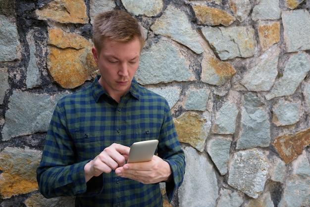 Jovem bonito usando telefone celular contra a parede