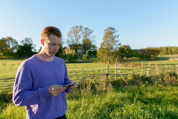Jovem bonito usando telefone celular em uma planície pacífica e gramada com a natureza