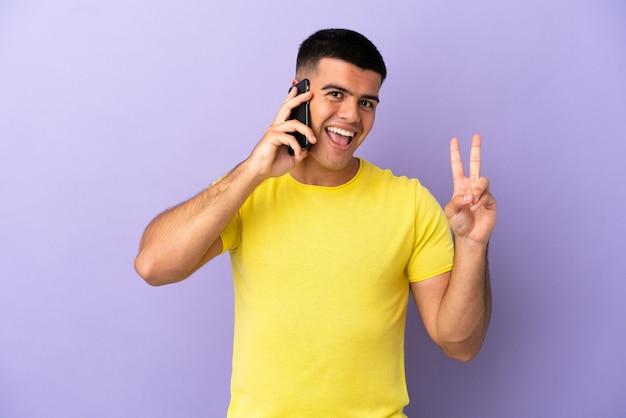 Jovem bonito usando telefone celular sobre fundo roxo isolado, sorrindo e mostrando sinal de vitória