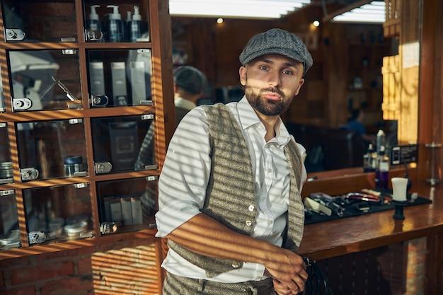 Jovem bonito usando um chapéu enquanto se inclina à mesa de uma barbearia