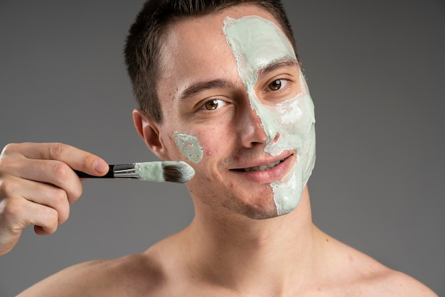 Jovem bonito usando uma máscara para acne