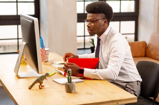 Jovem bonito verificando tudo enquanto faz seu trabalho com cuidado