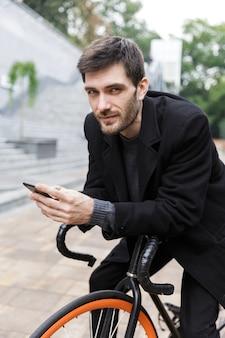 Jovem bonito vestido com um casaco encostado em uma bicicleta na rua, usnig telefone celular