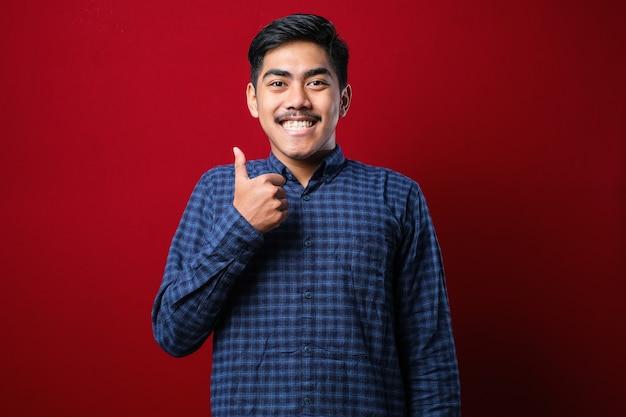 Jovem bonito vestindo camisa casual em pé sobre redbackground isolado, fazendo feliz polegares para cima gesto com a mão. expressão de aprovação olhando para a câmera mostrando sucesso.
