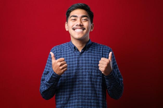 Jovem bonito vestindo camisa casual sobre fundo vermelho, aprovando o gesto positivo com a mão, polegares para cima sorrindo e feliz pelo sucesso. gesto do vencedor.
