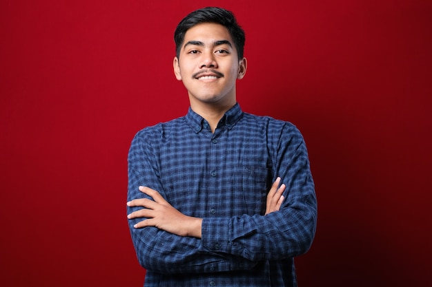 Jovem bonito vestindo camisa casual sobre fundo vermelho rosto feliz, sorrindo com os braços cruzados, olhando para a câmera. pessoa positiva.